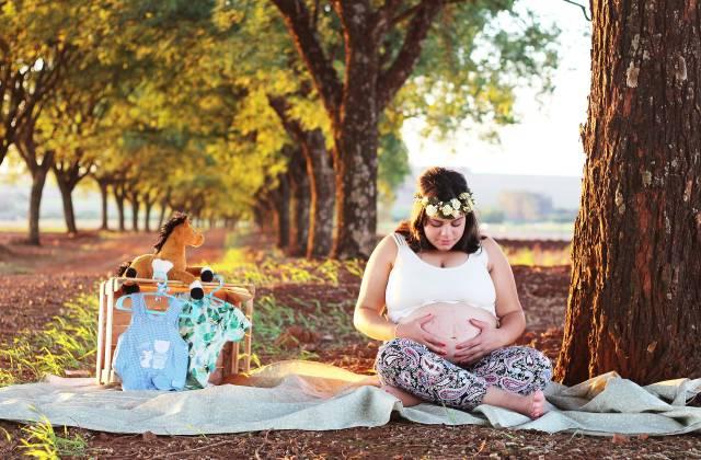 schwangere Frau sitzend auf einer Wiese