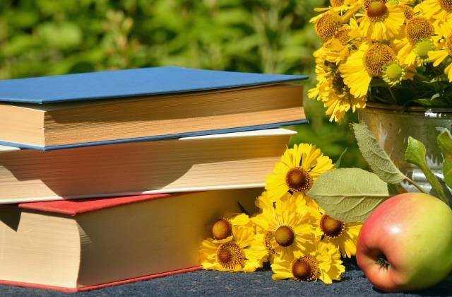 Blumen und Bücherstapel und ein Apfel